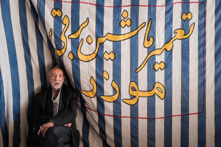 old man posing for a photo in the bazar of Kerman