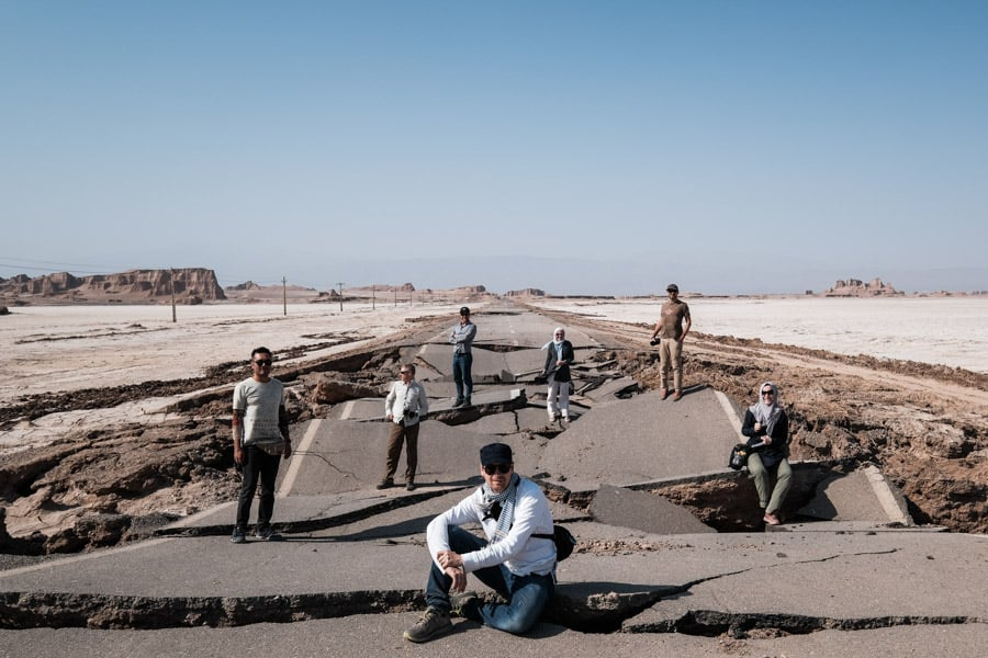 The photography tour group from pics of asia in iran poses in front of a broken road